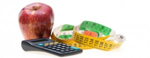 Pear, metric tape and calculator representing the overload